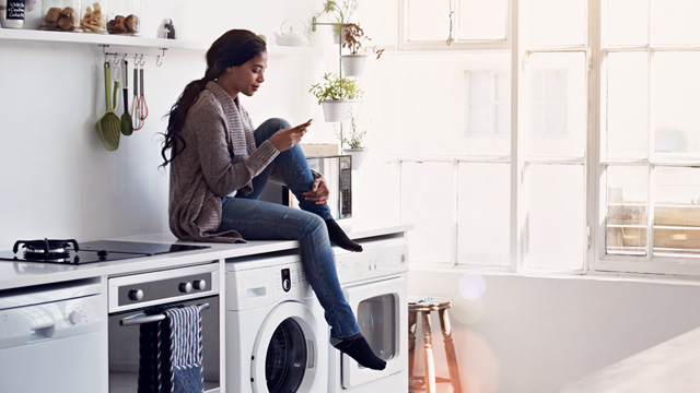 Woman sitting on washing machine