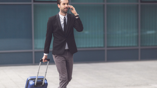 Man walking with a suitcase when talking in mobile