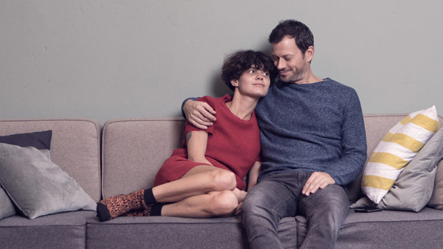 Couple sitting close to each other in a sofa