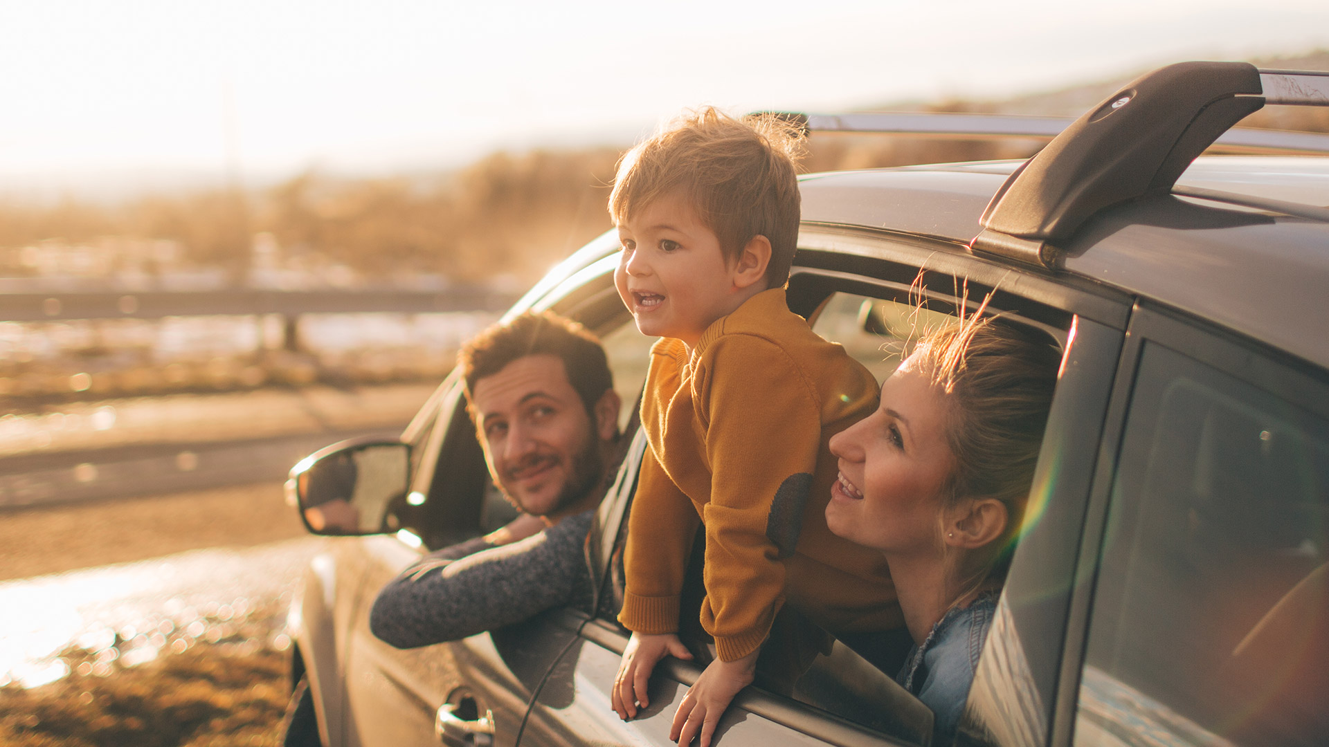 family in car kid leaning out of window