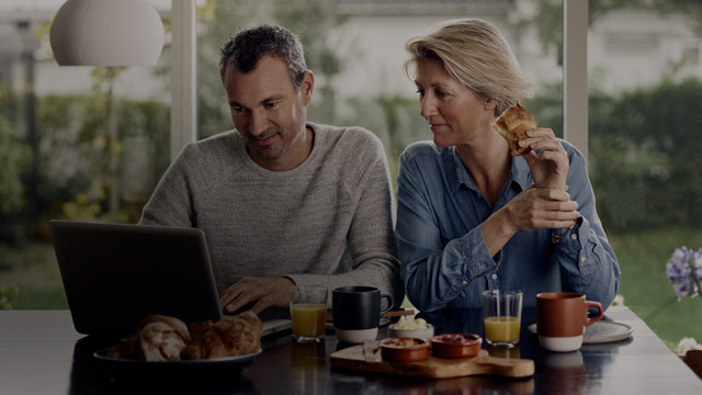 Couple eating breakfast looking at laptop small overlay