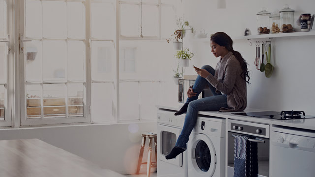 Young woman sitting on washing machine small overlay
