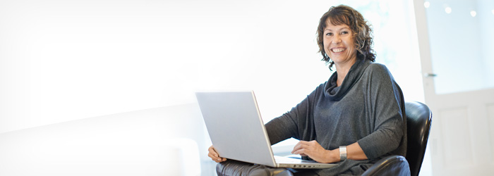 Smiling woman with laptop in her lap